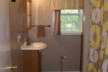 Bathroom with sink, tub/shower, toilet, linens, soap, and paper products.