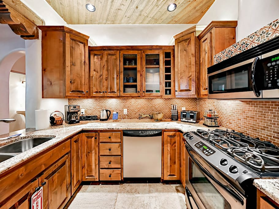 The well-equipped kitchen features granite countertops and knotty alder cabinets.