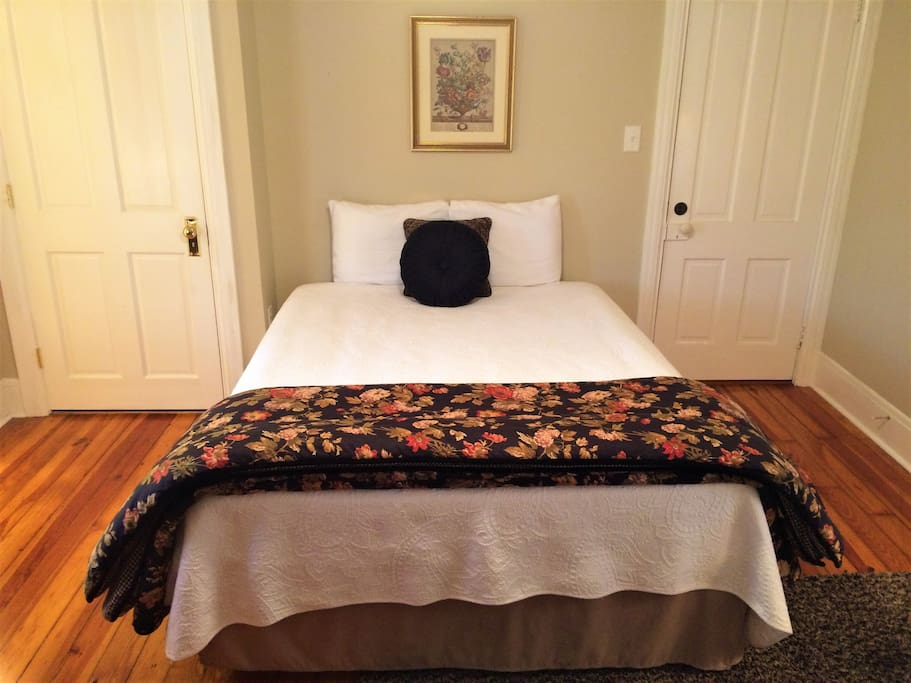 The cozy queen bed is dawned in beautiful linens and the hardwood floors coupled with delightful sunshine envelop the room in warmth.