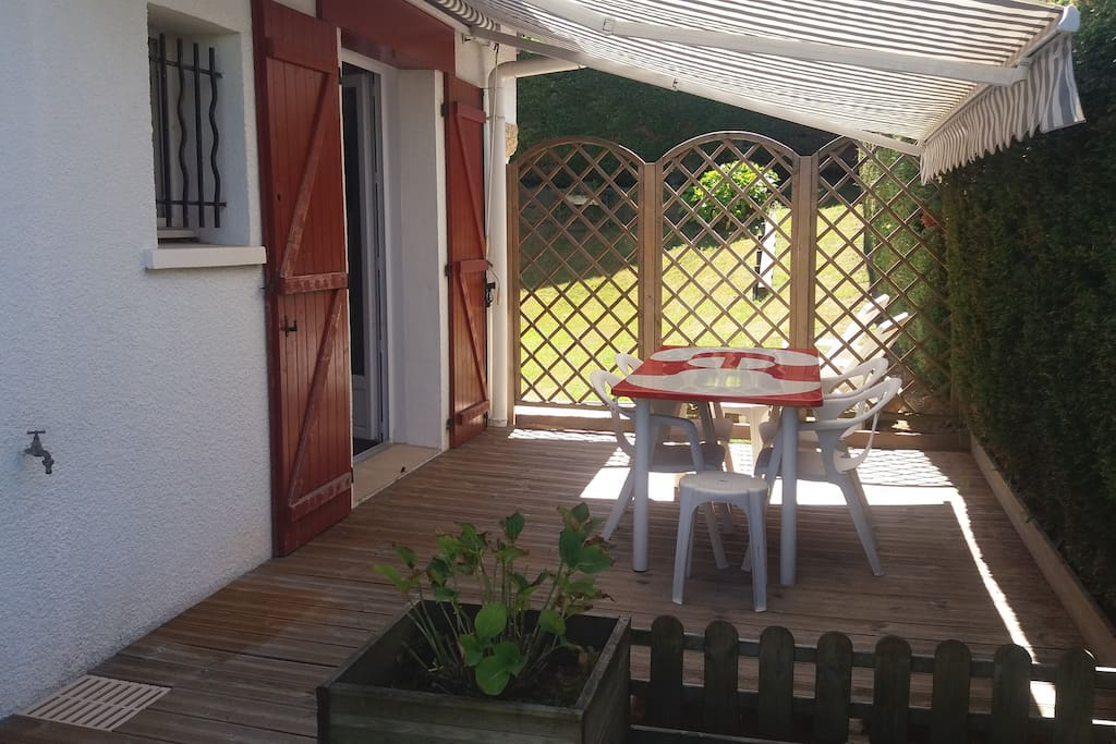 terrasse en bois avec table et chaises de jardin, store manuel