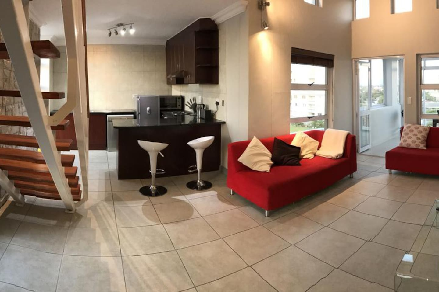 A spacious, modern, open-plan living area leads onto two bedrooms with shared bathroom and a staircase leads to the main ensuite bedroom and study upstairs.
