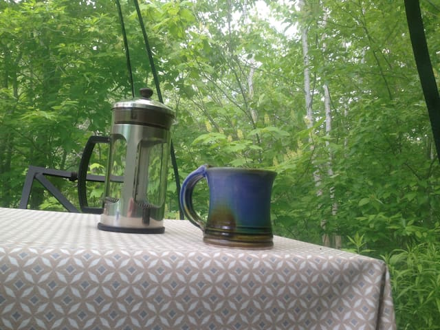 Enjoy your coffee in the dining tent surrounded by birch trees