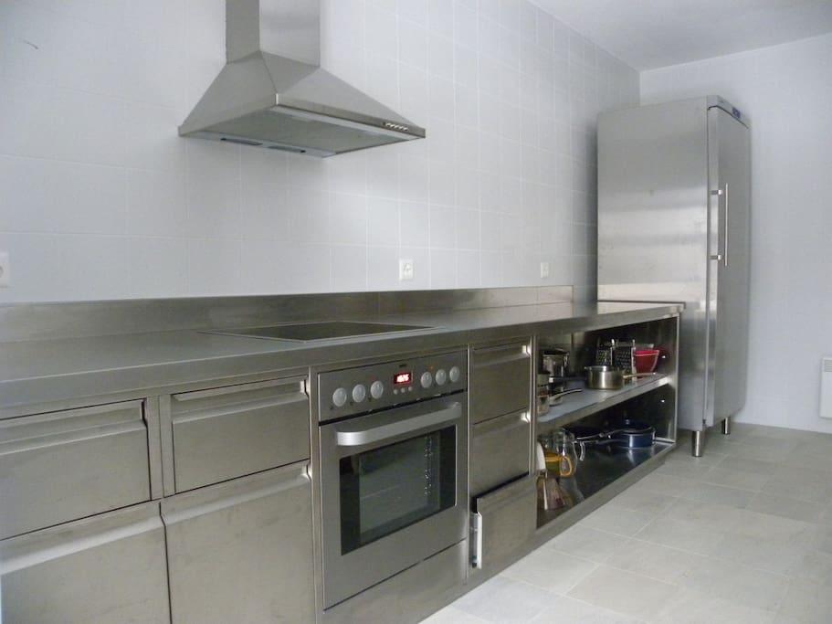 Moderne Chromstahlküche mit leistungsfähigem Geschirrspüler, Backofen, Kühlschrank
