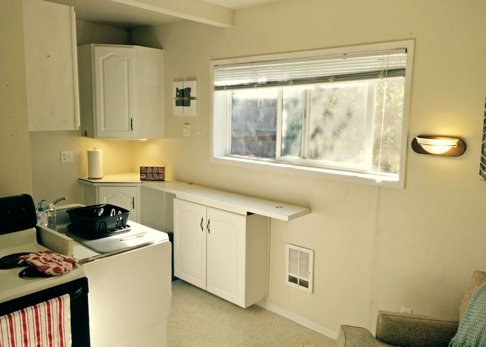 Looking from entry towards small kitchen space. The counters can be extended next to the stove for more space or a small table for two.