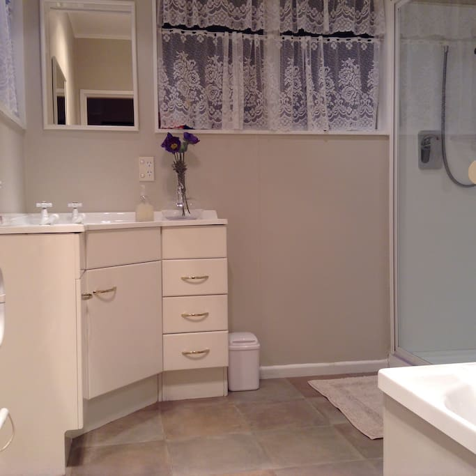 Large bathroom with shower and bath. Toilet in room next door.