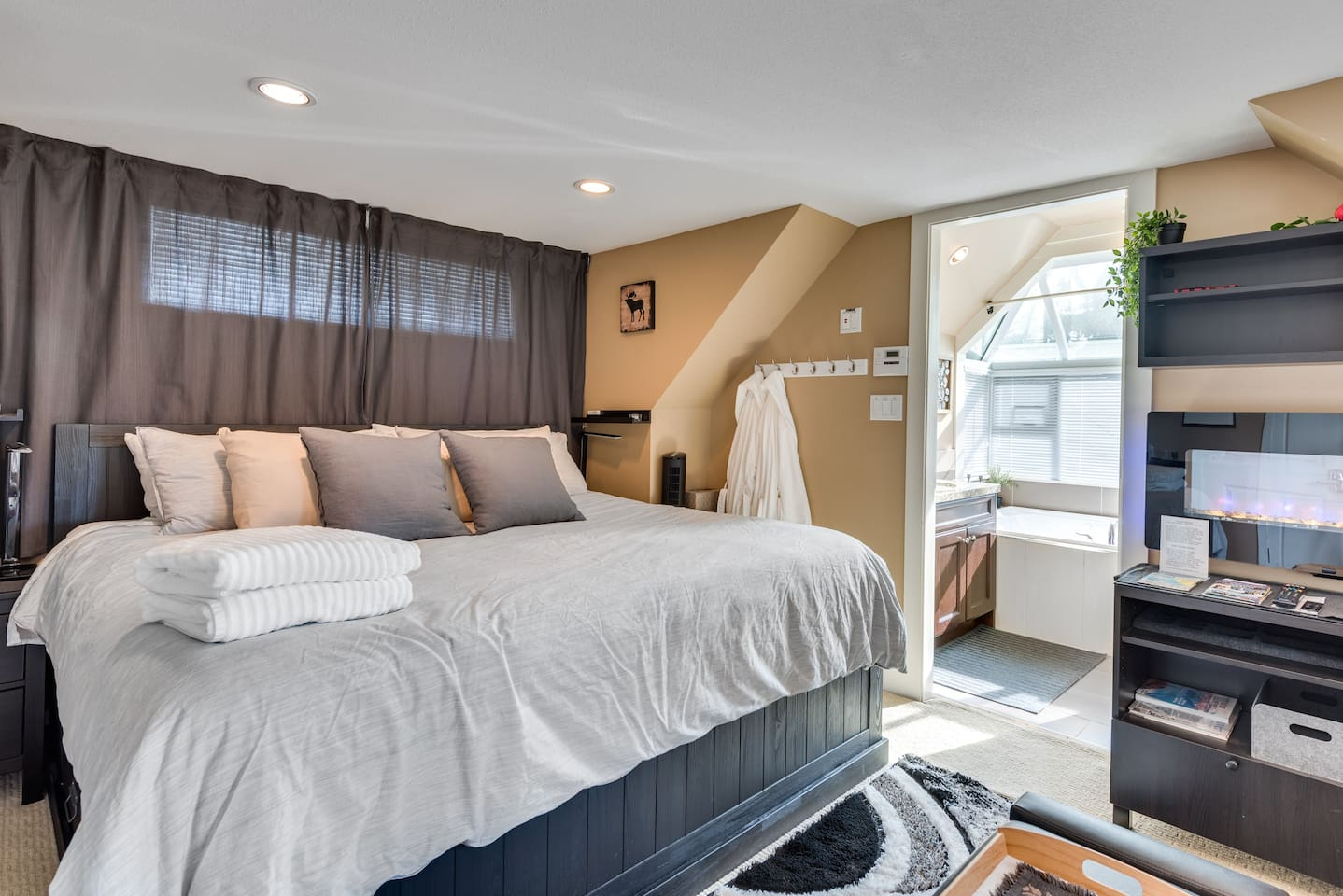 A comfy loft room in the heart of Central Lonsdale with ensuite jacuzzi bath, couch, TV, Keurig, fridge, microwave and comfy King Size bed loaded with pillows...