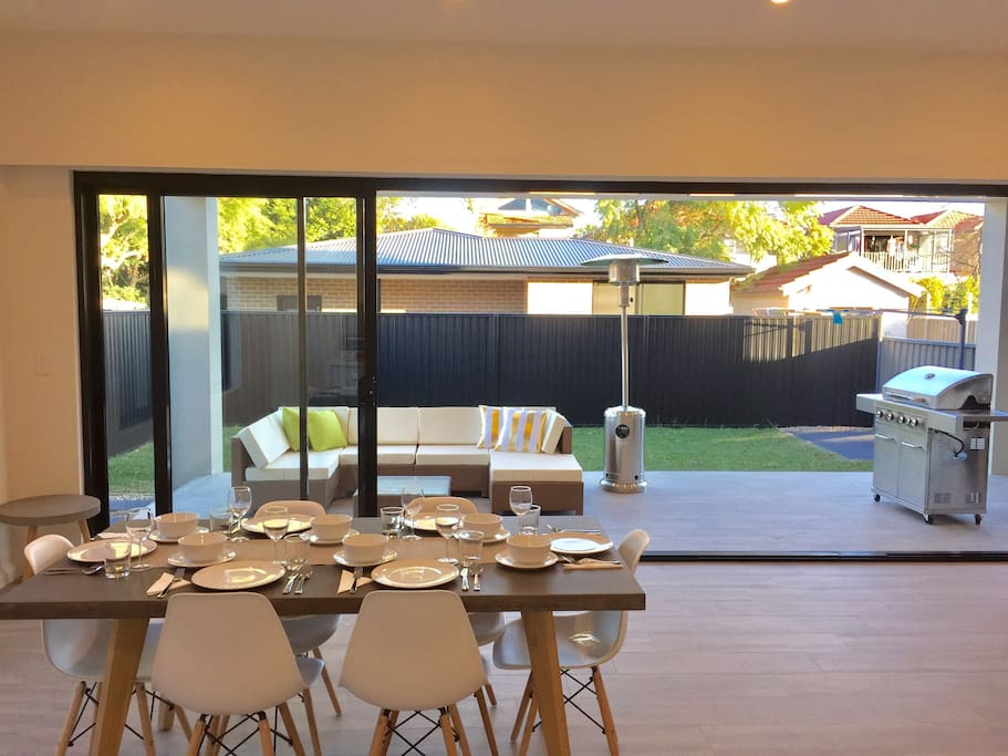 The spacious open-plan living and dining area leads straight through a set of floor to ceiling glass doors onto a tiled entertainer's terrace equipped with outdoor lounge, gas heater, and four-burner barbecue