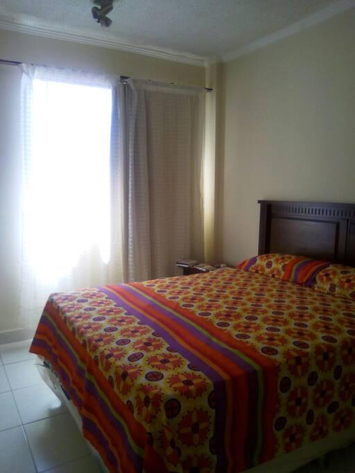 Habitación principal, confortable, Somier 2 personas. Colchón de primera calidad. Incluye vestier, posee ventanal antisolar con vista entrada principal del edificio.