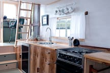 Fully equipped galley kitchen with gas stove, fridge, and service for four