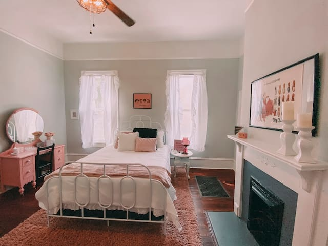 """The """"Pink Ladies"""" bedroom is a retro dream. You will find one of a kind antique furnishings with a new modern queen sized bed."""