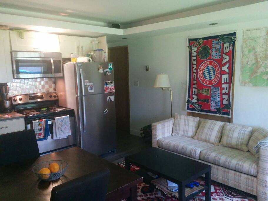 Living room with comfortable couch & coffee table. Located next to the kitchen & hallway, which provides access to the bedrooms (yours & mine) and bathroom.