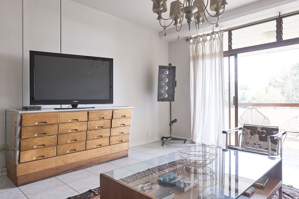Large screen TV in lounge with assorted cable channels.