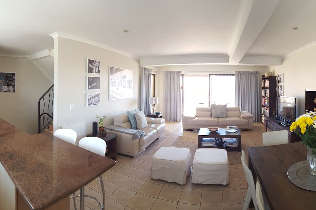 Wide angle view of the 2nd floor. Kitchen, dining area, TV lounge and balcony.