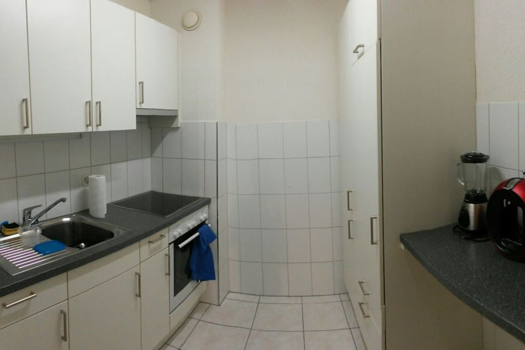 Kitchen with big fridge, coffee machine, kettle and blender.