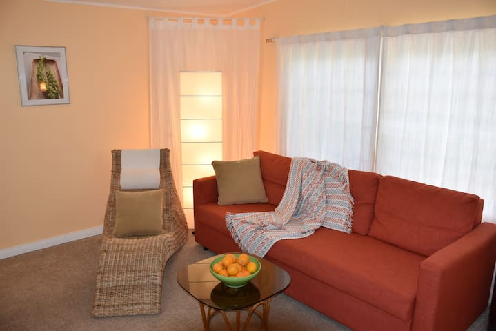 The living room is equipped with a bed couch, coffee table/ ottoman, a lounge chair with cozy pillows and throws to snuggle up after a busy day in town or on the trails.