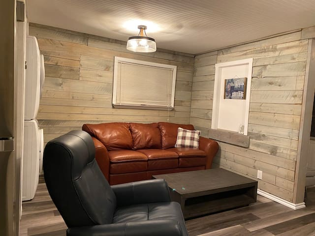 This is the living room area with leather couch and leather power recliner/rocker.  The walls are original shiplap giving the room a warm rustic feel.