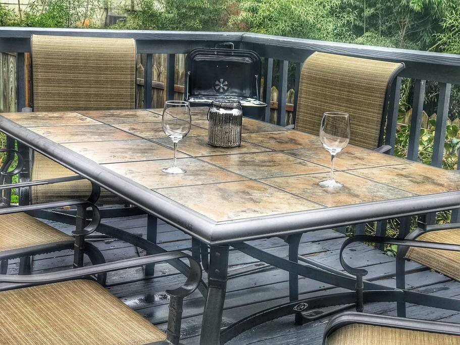 Patio table with 6 chairs and a grill.