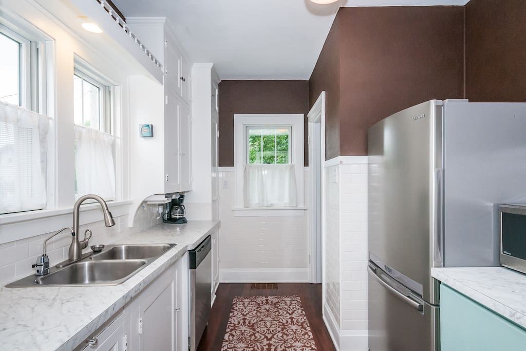 Main floor: Kitchen is equipped with refrigerator, stove, microwave, dishwasher, and coffee maker.