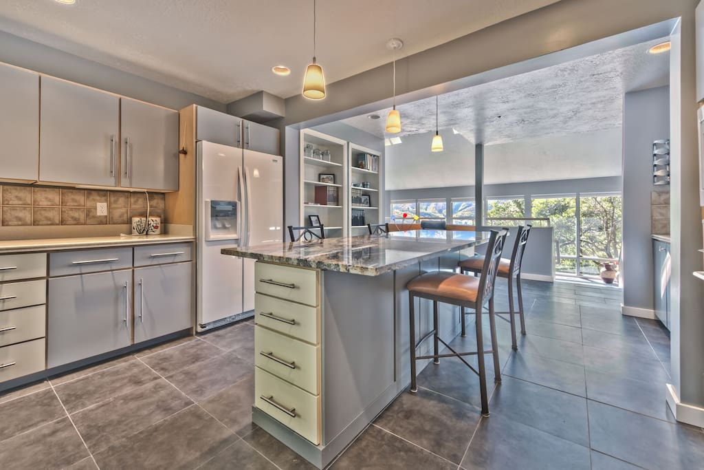 Fully Equipped Kitchen with a 5-Burner Gas Stove and an Island with Bar Seating