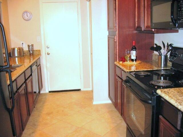 Kitchen with granite countertops, appliances (coffee maker, blender, toaster etc), spices, utensils, pots, pans, bake ware.