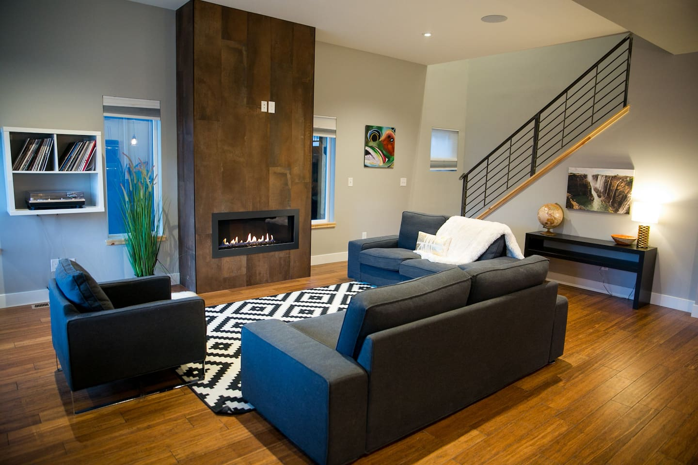 The living room area features a gas fireplace and the stairs have a custom welded steel handrail.