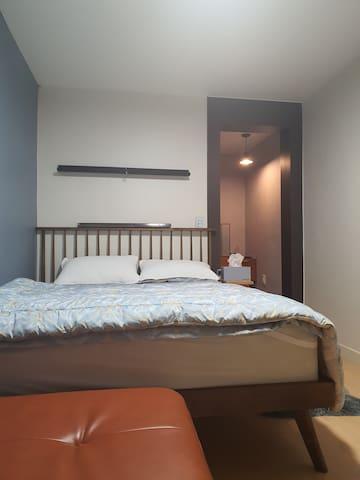퀸 침대, 에어컨, 사운드바 가 있는 침실입니다.