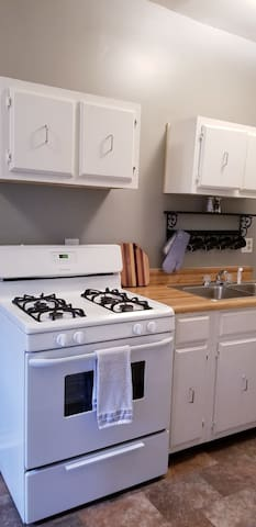 A kitchen with a gas stove and all amenities for cooking at the apartment