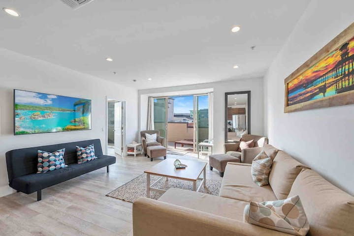 """Living area with two convertible sofa beds, two chairs and foot stools, 65"""" smart tv, 400Mbs WiFi and an adjoining private balcony with great ocean, beach, pier and gorgeous HB sunset views!"""