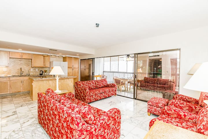 """LR/kitchen/ breakfast bar & view of 10'x24'  screened lanai with new DR table & 6 chairs.  New Kawai piano & 65"""" smart TV, with cable & Wifi.  New refer with filtered water/ice in door.  Two queen sleeper sofas.  Beach across street & 30+restaurants"""