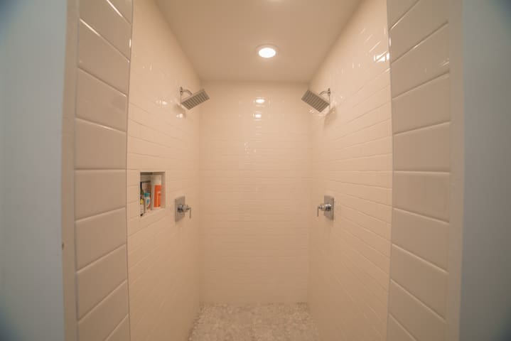 Two shower heads in fully tiled master shower
