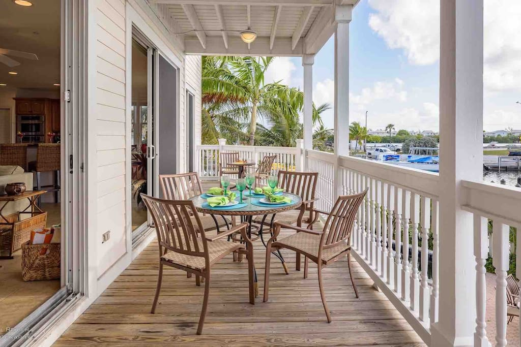 The spacious porch has an outdoor dining set for four and overlooks the water...