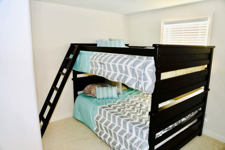 Guest bedroom with full over full bunk bed, built in wall dresser and flat screen TV