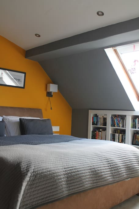 Spacious bedroom with a superking bed, floating shelves either side of the bed and a mini library.