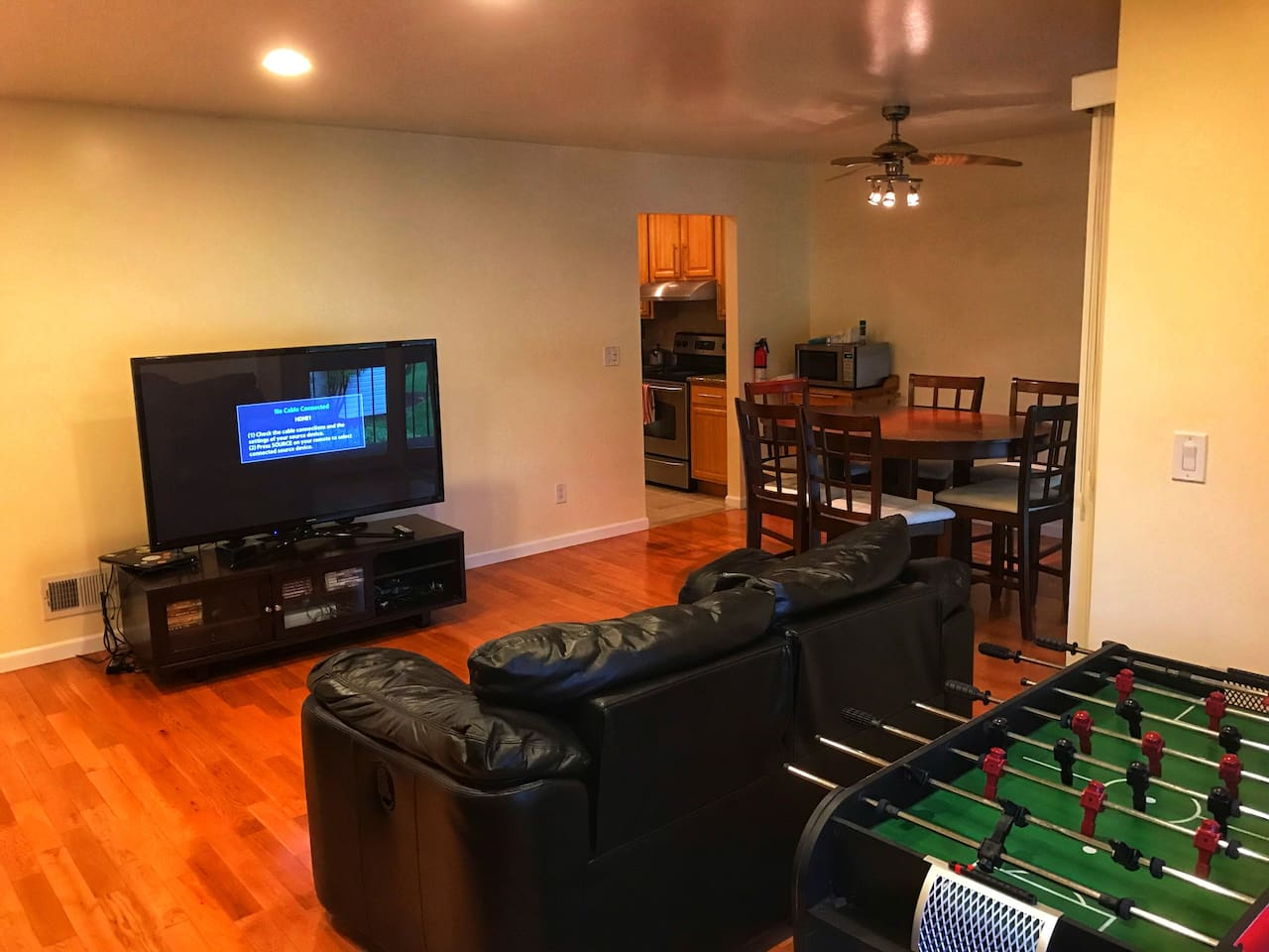 Living room with the kitchen in the back; Microwave, dining table, foosball table, 60 inch TV with fire stick, Xbox 360 & Xbox original
