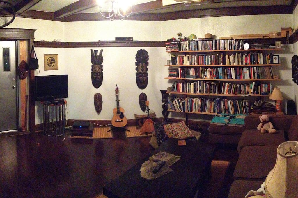 Eclectic den with massive bookshelf (mainly fiction, non-fiction, poetry, art, comics, and several dvds), guitar, comfy couch, African decorative items, access to kitchen and fire escape platform for smoking and fresh air)