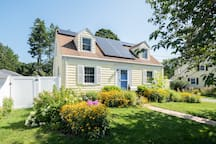 Charming home surrounded by gardens and flowering trees.
