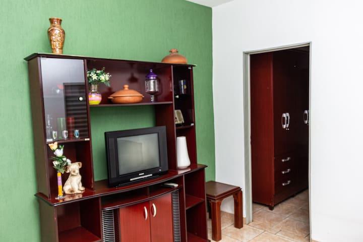 Sala com TV e espaço para colchões