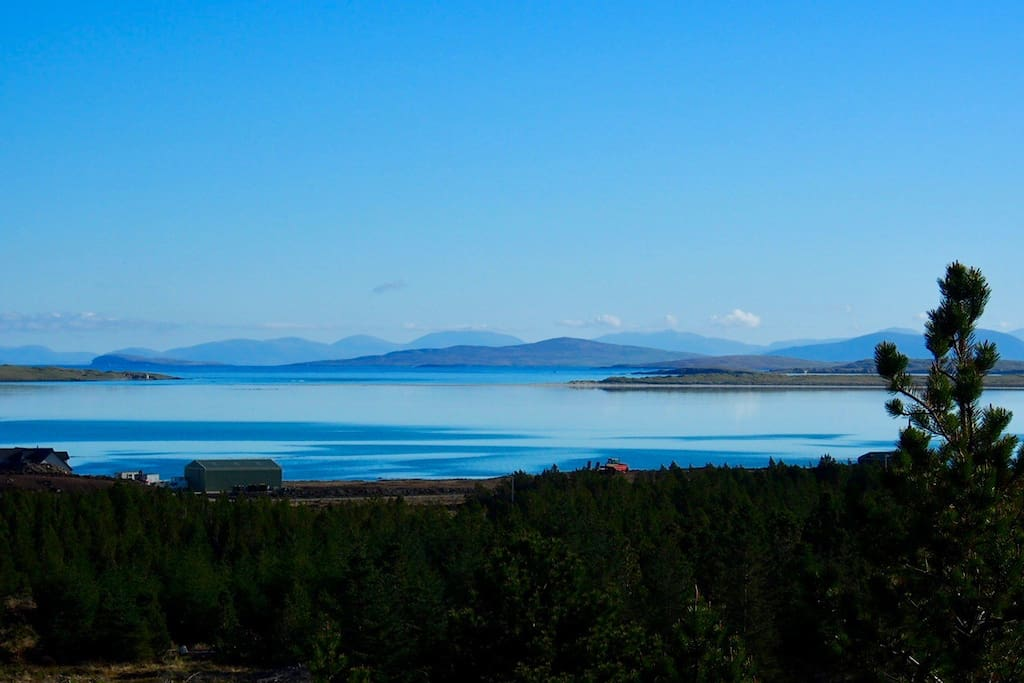 Views over the treetops to the tidal sands of Claddach Vallay and the hills of Harris