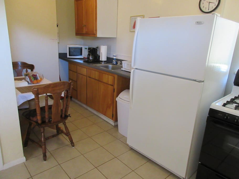 Microwave, full-size refrigerator, and oven range in the kitchen. Dishes and utensils provided, and a two-seat dining area.