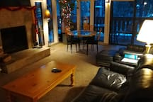 Downstairs living room with mounted flat screen TV, large indoor fireplace and dining table.