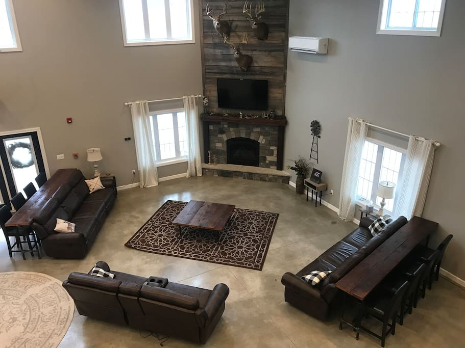 Great Room living area with gas fireplace, satellite TV and seating for 8 at couch tables.