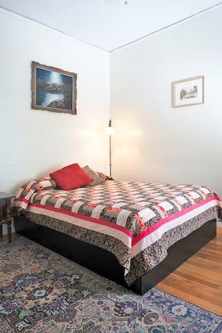 Your bedroom! Nightstand, dresser/vanity and lockable door with lovely sunny windows.