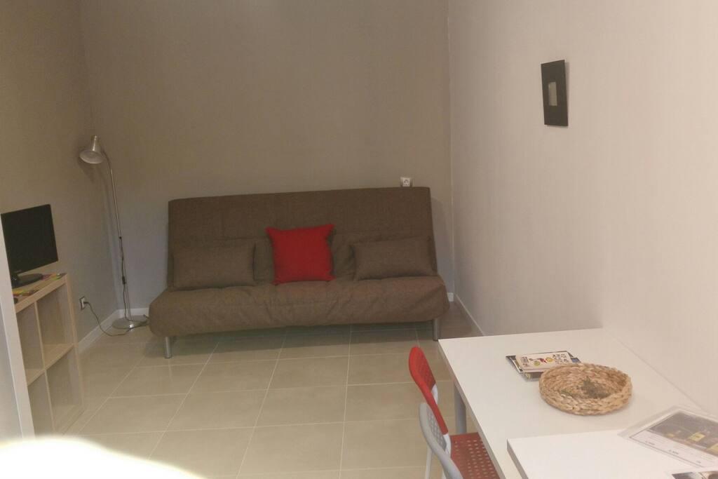 sofa llit. moble amb tv. taula i cadires.
