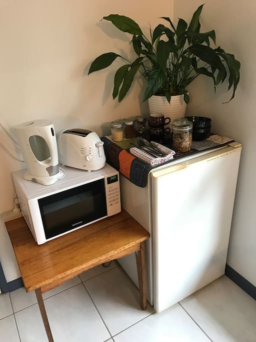 A homemade breakfast, with fresh  fruit and milk, coffee and tea makings, plus a microwave, kettle and toaster.