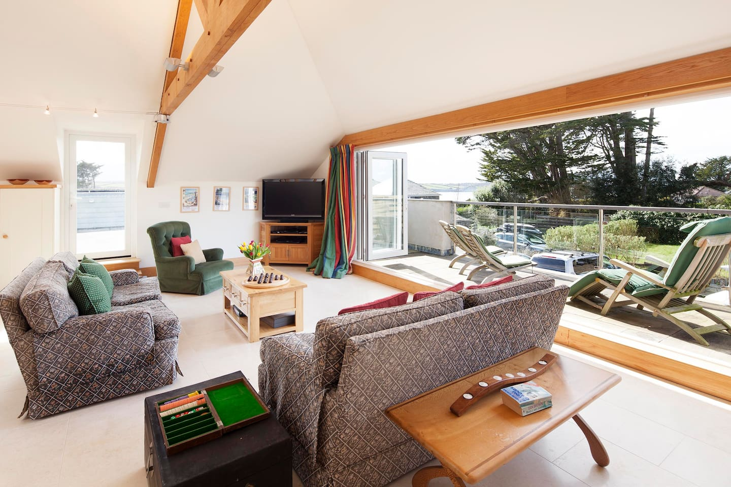 The light and airy living room with the front deck looking out to Porthilly Cove below