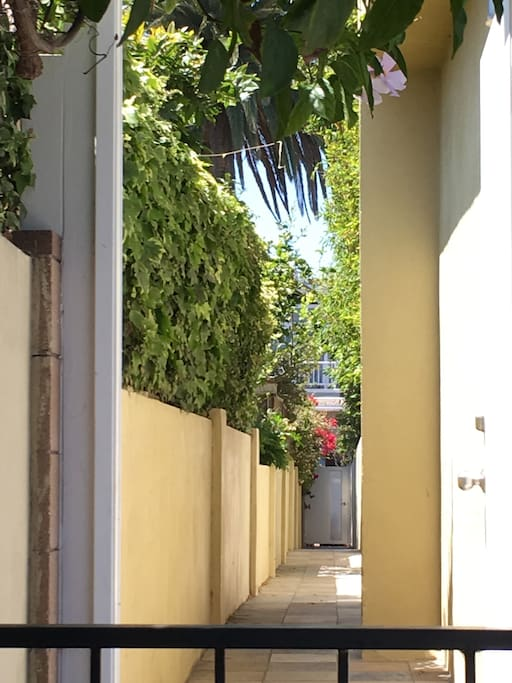 After you open the back gate near the cars with your key, you'll see this long corridor to the other side of the property.  The apartment is up the staircase to the right.