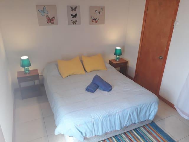 El dormitorio principal se encuentra en la planta baja de la casa, esto para brindarte mayor independencia y privacidad. Cuenta con cama de 2 plazas, 2 veladores, 2 lámparas, closet y repisa. Tiene salida directa al patio.