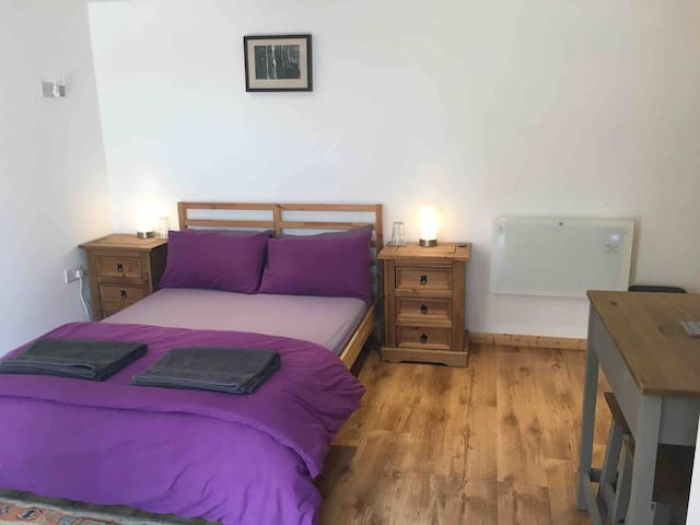 Double bed with bedside tables and lamps.