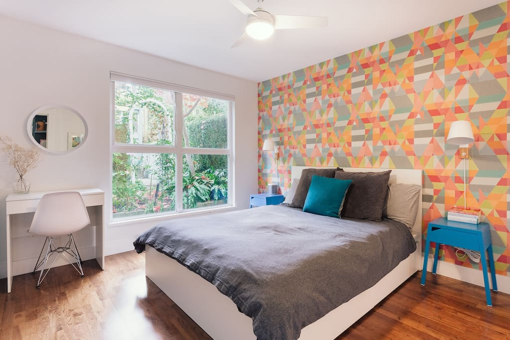 Primary bedroom featuring queen size bed, private garden views and ensuite bathroom