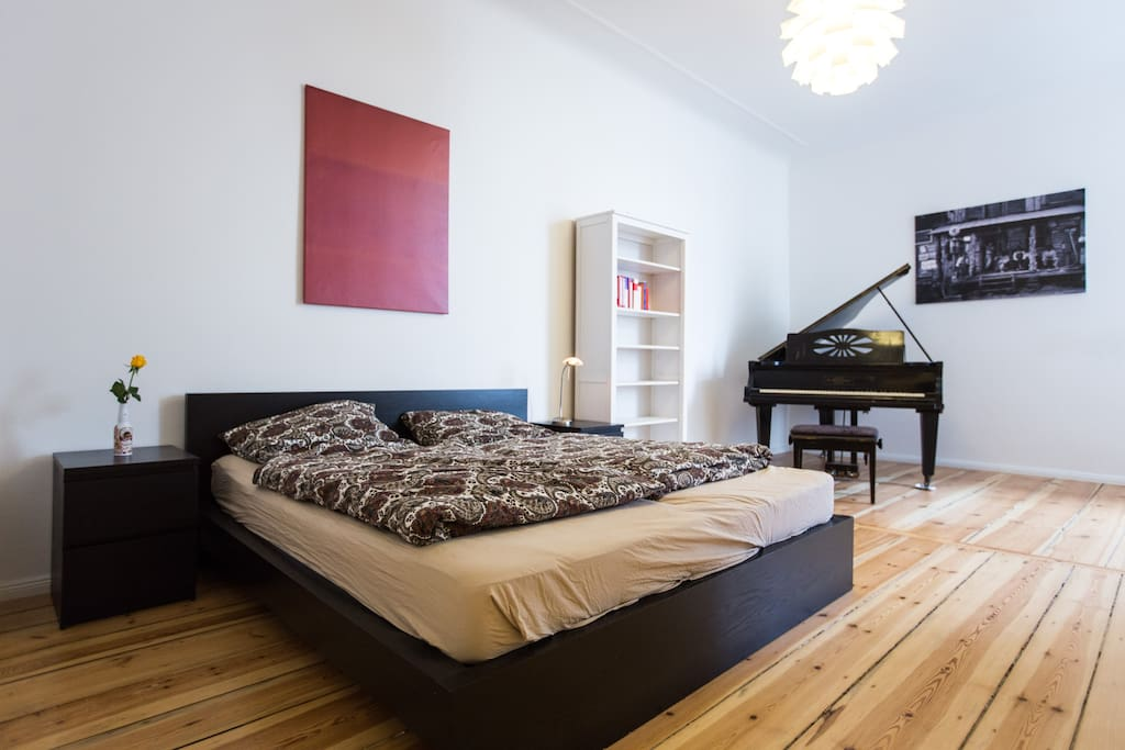 Bedroom with kingsize bed and piano
